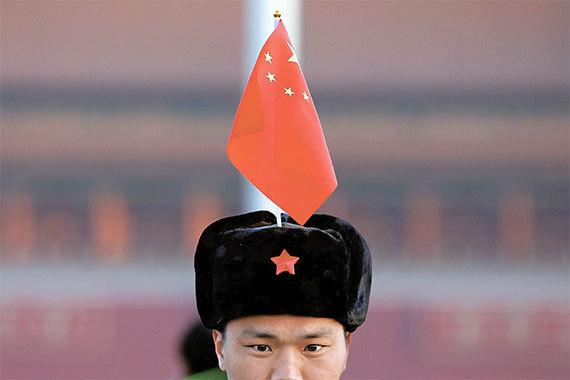 오는 5일 개막하는 전국인민대표대회와 함께 중국 최대의 정치 행사인 전국인민정치협상회의가 3일 베이징 인민대회당에서 개막했다. 이 행사에는 시진핑 국가주석과 리커창 총리 등 정치국 상무위원 7명이 모두 참석했다. 이날 한 남성이 중국 국기를 자신의 모자에 꽂고 천안문광장을 지나고 있다. [베이징 로이터=뉴스1]
