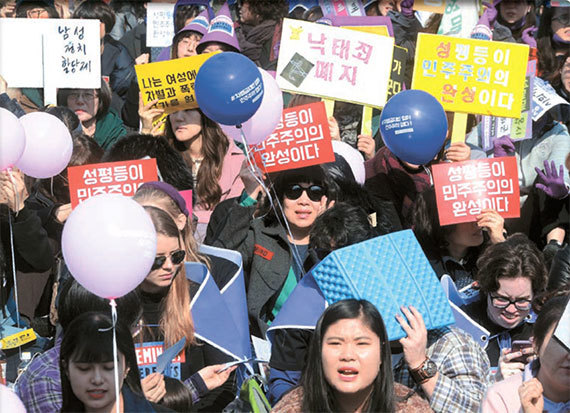 지난 4일 서울 종로구 보신각에서 열린 3·8 여성의 날 기념 '2017 페미니스트 광장' 행사에서 참가자들이 피켓을 들고 '성평등이 민주주의 완성이다'라고 구호를 외치고 있다. [뉴시스]