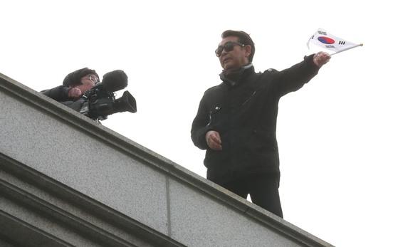 박근혜 전 대통령 자택 앞 건물 옥상에서 취재중인 방송사 카메라 렌즈를 태극기로 가리는 박 전 대통령 지지자.