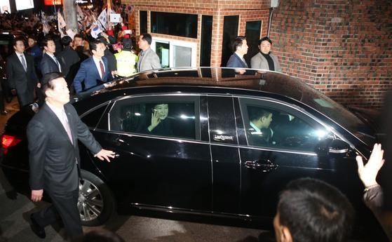 저녁 7시36분 쯤 자택에 도착한 박 전 대통령이 차안에서 손을 들어 지지자들에세 인사를 하고 있다.
