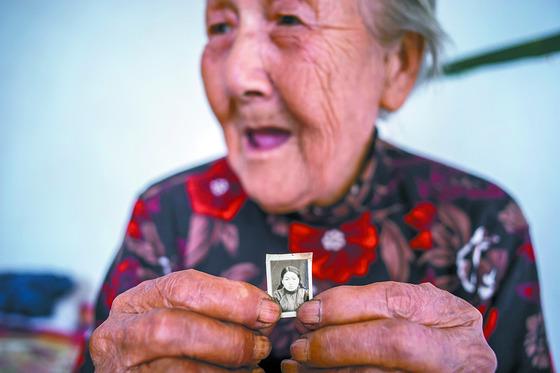 안세홍 작가가 찍은 이 사진 속 주인공은 일본군 위안부의 중국인 피해자인 카오 헤이마오(95)씨. 할머니는 20대 시절의 증명사진을 내보이며 일본군이 앗아간 꽃다운 청춘을 떠올렸다. [사진 안세홍 작가]