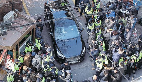 """13일 박근혜 전 대통령 삼성동 자택에서 승용차 한 대가 나오고 있다. 박 전 대통령 지지자들은 이날도 자택 앞에서 """"탄핵 무효""""를 외쳤다. [사진공동취재단]"""