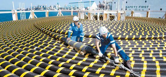 LS그룹은 친환경적인 에너지 효율 기술 상용화에 박차를 가하고 있다. LS전선은 최근 당진과 평택을 잇는 육상 HVDC 케이블 사업을 수주했다. LS전선 동해사업장 엔지니어들이 카타르 석유공사에 납품할 해저케이블 완제품을 살피고 있다. [사진 LS]