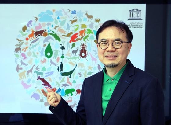 동식물로 웃는 얼굴의 지구를 표현한 '생물종다양성의 해' 포스터를 든 왕종두씨. [사진 최정동 기자]
