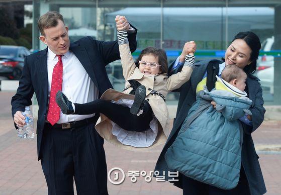 로버트 켈리 교수와 부인 김정아씨가 15일 부산대 캠퍼스에서 딸 매리언을 손그네 태우고 있다. 김씨가 안고 있는 아이는 9개월 된 아들 제임스. [부산=송봉근 기자]