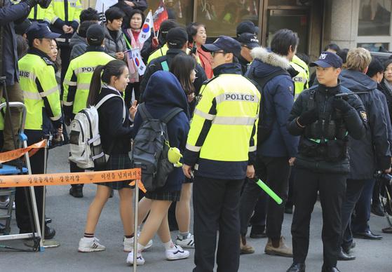 하교하는 학생들이 16일 오후 서울 삼성동 박근혜 전 대통령 자택 앞을 경찰의 안내를 받으며 지나가고 있다. [사진 임현동 기자]