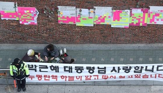 15일 오전 서울 강남구 삼성동 박 전 대통령 자택에서 박 전 대통령 지지자들이 담벼락에 매달 꽃을 다듬고 있다. [사진 공동취재단]
