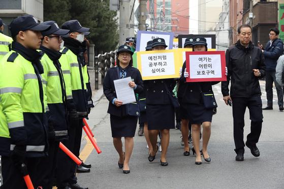 삼릉초등학교 녹색어머니회 회원들이 20일 오전 박 전 대통령 자택 앞에서 학생 안전 등을 요구하며 행진하고 있다. 우상조 기자