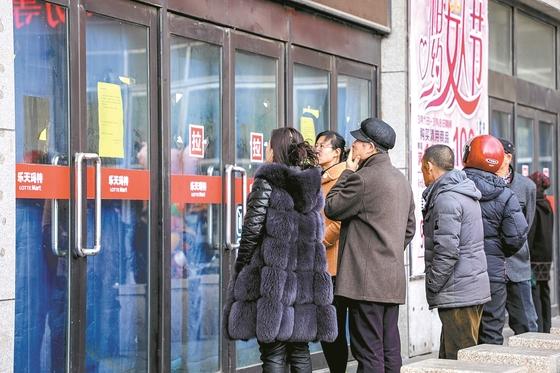 영업정지를 당한 롯데마트 중국 단둥 지점 앞에서 3월 5일 시민들이 매장 안을 보고 있다. [사진 중앙포토]