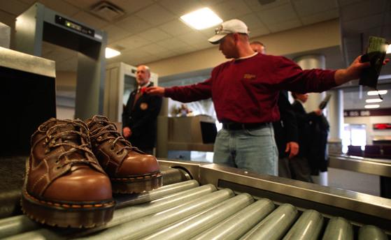 공항에서 신발 등 보안검색을 거치는 승객들. [AP=뉴시스]