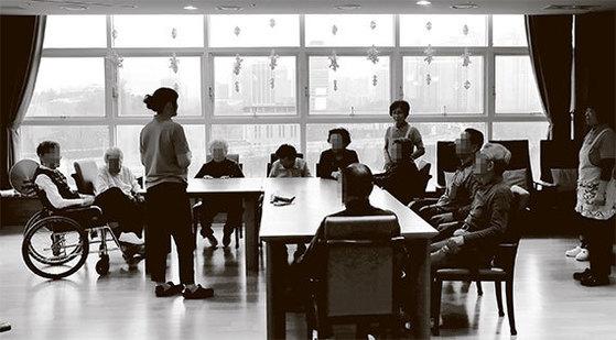 초기 치매 등 경증 질환을 앓고 있는 노인들이 21일 서울 강동구 KB골든라이프케어센터에서 열린 신체감각프로그램에 참석해 설명을 듣고 있다. [사진 김춘식 기자]