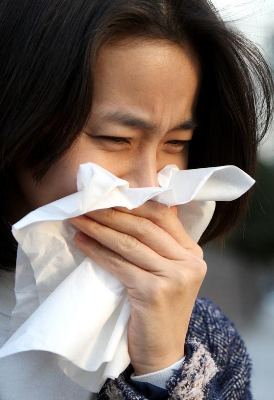 휴지로 코와 입을 막고 재채기 하는 여성. [중앙포토]