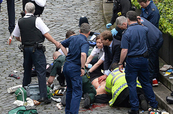 비아스 엘우드 영국 외무차관(가운데)이 22일 런던 테러 현장에서 쓰러진 시민에게 응급처치를 하고 있다. [AP=뉴시스]