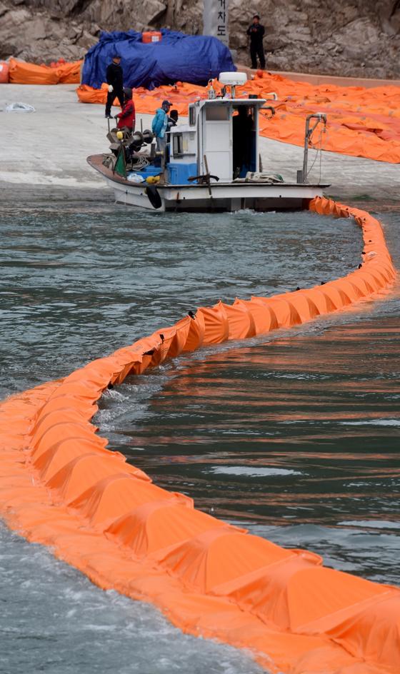 세월호 인양이 시작된 23일 진도 동거차도 어민들이 세월호 기름유출을 막기위해 사고 해역 주변에 기름막를 설치하고 있다. [사진 중앙포토]