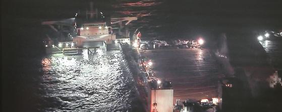 재킹 바지선 두대에 묶여 인양중인 세월호가 24일 밤 진도 앞바다에서 반잠수식 선박에 선적되고 있다.[사진 KBS 캡처]