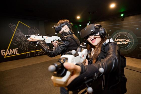 롯데월드 어드벤처의 VR 체험 어트랙션 '서바이벌 모탈블리츠'. 헤드기어를 착용하고 화면 속 괴물을 총으로 쏴 물리친다. [사진 롯데월드 어드벤처]