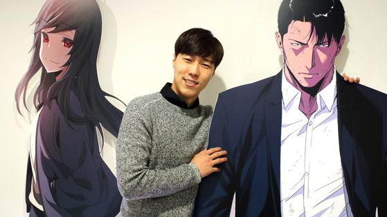 유정석 대표를 최근 서울 구로구 디지털로에 있는 탑코 사무실에서 만났다. 그가 탑툰의 대표 웹툰 '청소부K'의 캐릭터 입간판과 포즈를 취했다. [사진 김춘식 기자]