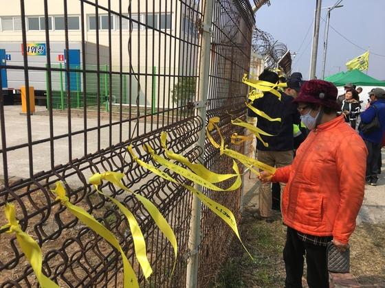 목포 신항만 출입을 통제하는 철조망 사이사이에 묶인 노란 리본들. 하준호 기자