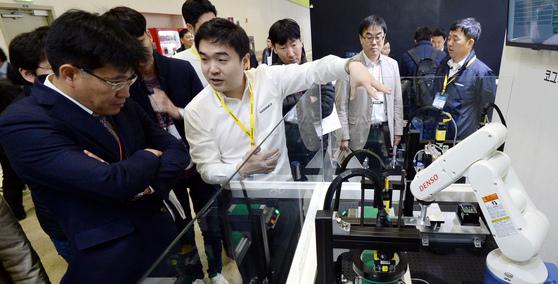 29일 서울 삼성동 코엑스에서 열린 '2017 스마트공장·자동화 산업전'에서 관람객들이 제품 불량률을 줄이는 산업 로봇에 대한 설명을 듣고 있다. [뉴시스]