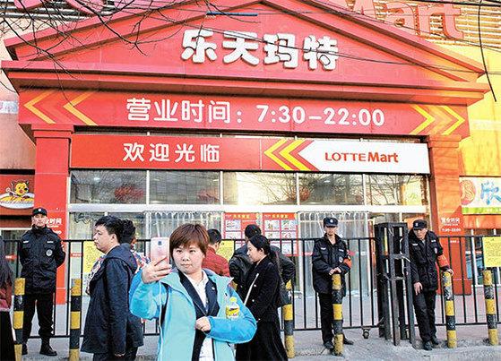 지난달 13일 중국 베이징에서 한 여성이 영업정지된 롯데마트를 배경으로 셀카를 찍고 있다. 중국 당국은 지난달 초 중국 내 롯데마트 점포 60여 개에 소방규정 위반을 이유로 영업정지 처분을 내렸다. [AP=뉴시스]