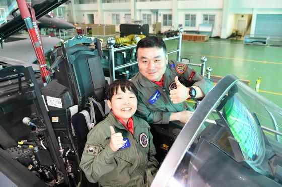심규휘군(왼쪽)이 F-15K 전투기에 탑승한 뒤 환하게 웃으며 엄지를 치켜 세우고 있다. 심군의 오른쪽엔 체험 안내를 맡은 전투조종사 이동영 소령. [사진 공군]