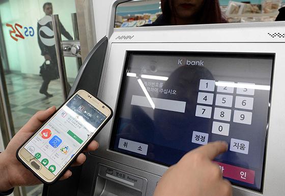 서울 종로구 한 편의점에서 고객이 인터넷 전문은행 앱을 활용해 무카드 송금 서비스를 이용하고 있다. 공인인증서 없이 활용할 수 있는게 장점이다. [뉴시스]