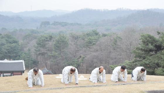 벌초를 시작하기 전 인부들이 왕릉을 향해 절을 하고 있다