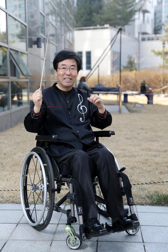 사고로 하반신 마비가 된 세한대 실용음악과 정상일 교수. 장애를 극복한 그는 휠체어 장애인 합창단을 지휘하고 있다. 3일 오후 서울 순화동 배재빌딩 근방의 조형물 앞에서 포즈를 취했다. 우상조 기자