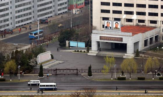 북한이 마시일을 발사한 5일 아침 평양 시내에 위치한 김책공업대학 앞을 시민들이 봄비에 우산을 받쳐든 채 지나가고 있다.사진공동취재단