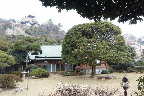 이훈동정원 안에 있는 일본풍 주택과 앞마당. 뒤로는 유달산 대학루(왼쪽 정자)와 노적봉(오른쪽 암봉)이 보인다. 마당의 큰 나무는 후박인데 수령이 250년쯤 된다고 한다. 드라마 '모래시계'에서 배우 고현정이 가지에 맨 그네를 타던 나무다.