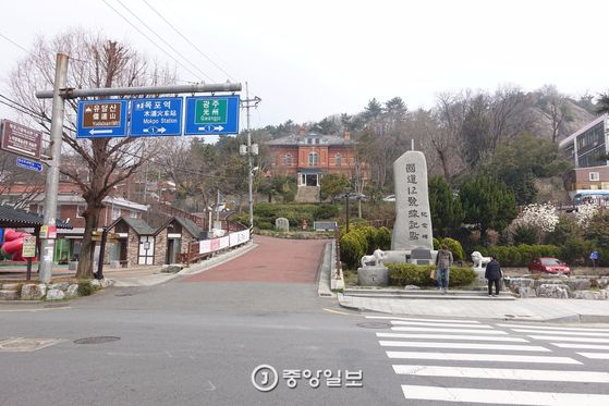국도 1,2호선의 옛 기점을 알리는 비석. 지금은 도로가 연장돼 기점이 옮겨지는 바람에 '기념비'로 신분이 바뀌었다. 그 뒤로, 유달산 노적봉 아래 목포 평화의 소녀상과 근대역사관(옛 일본영사관)이 보인다.
