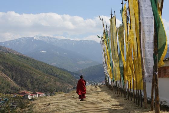 히말라야 설산이 보이는 길을 한 학승이 걷고 있다.