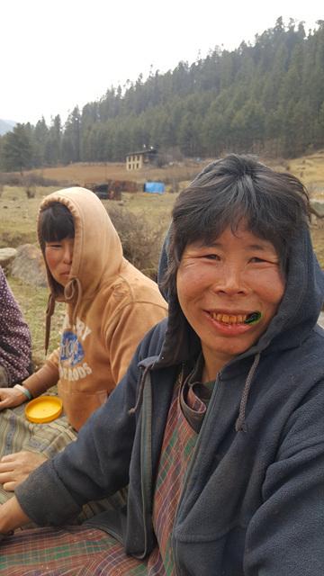 딱정벌레 너트 '도마'를 라임 잎에 싸서 씹고 있는 부탄의 아낙. 붉은 너트를 많이 씹으면 치아와 입술도 빨갛게 물든다.