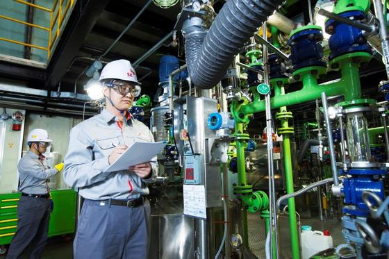 대전 SK바이오텍 공장에서 직원들이 파이프라인으로 물질을 흘려보내는 방식으로 약효물질을 배합하는 저온연속공정 설비를 살펴보고 있다. [사진 SK바이오텍]
