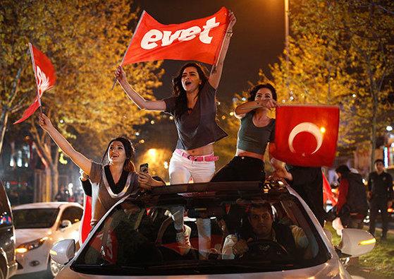 에르도안 지지 여성이 개헌안 찬성을 의미하는 터키어 'evet' 깃발을 들고 기뻐하는 모습. [로이터·AP=뉴스1·뉴시스]