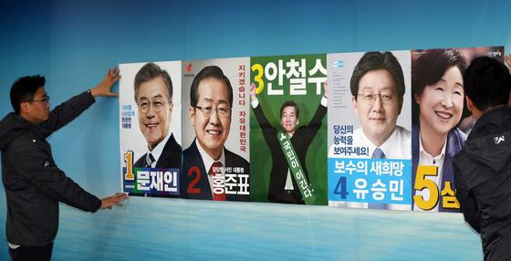 서울시선거관리위원회 직원들이 18일 오후 서울 종로구 서울시선관위로 일부 접수된 대선 후보자들의 선거벽보를 살펴보고 있다. 사진 김경록 기자