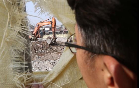 서울시 특별사법경찰이 지난 13일 서울 은평구 재건축 철거현장에서 미세먼지 발생 상황을 적발하기 위해가림막 구멍으로 현장을 살피고 있다. 공사장 비산 먼지는 수도권 미세먼지의 22%를 차지한다. [김상선 기자]