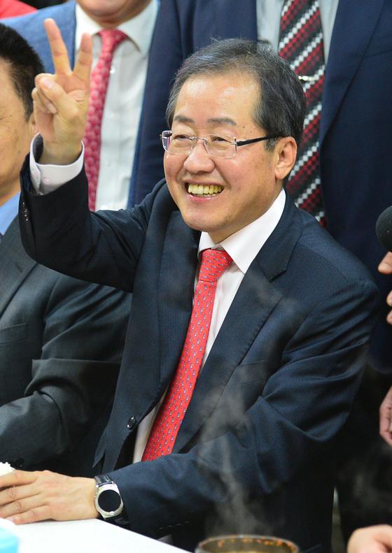 홍준표 자유한국당 후보가 18일 부산 서면시장을 찾아 손가락으로 V자를 그리고 있다. [송봉근 기자]