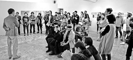 지난 3일 4·3미술제 전시장 중 한 곳인 제주시 '아트스페이스C'를 찾은 관람객들이 정용성 작가의 설명을 듣고 있다. [사진 4·3미술제 운영위원회]