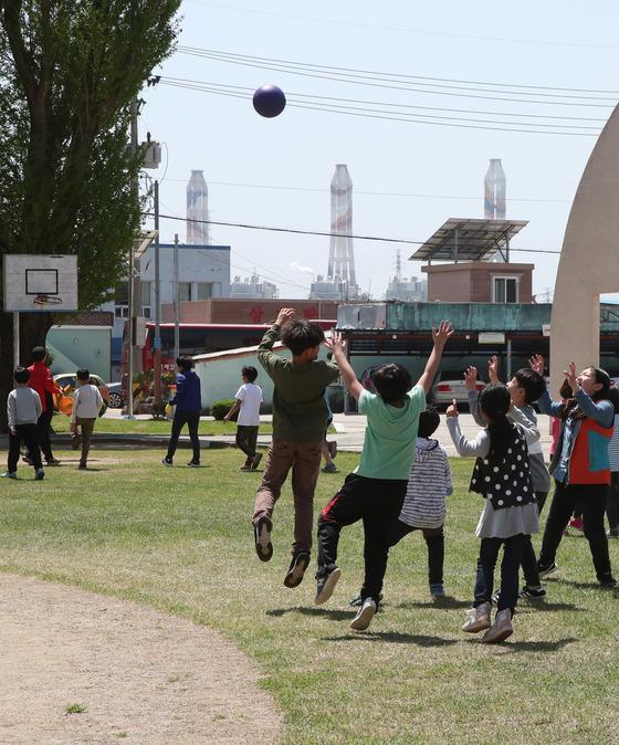 19일 경남 고성군 하이초등학교 학생들이 쉬는 시간 운동장에서 공놀이를 하고 있다. 뒤로 보이는 것이 삼천포화력발전소다. 송봉근 기자