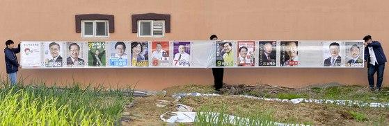 사진=김성태. 제19대 대통령 선거에는 역대 대선 가운데 가장 많은 15명의 후보가 출마했다. 선관위 직원들이 선거 벽보 부착에 앞서 약 10미터 길이의 벽보를 제보고 있다.