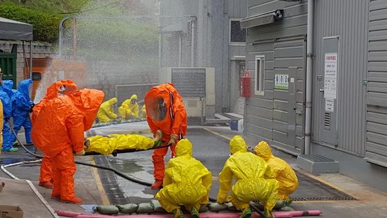 20일 충남 천안에서 열린 유해화학물질 유출사고 가상훈련에서 공장 직원과 소방대원들이 유해물질을 제거하고 있다. 천안=신진호 기자