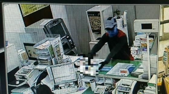 20일 오전 경북 경산시 남산면 자인농협 하남지점에서 한 괴한이 총을 들고 직원들을 위협하고 있다. [사진 경산경찰서]