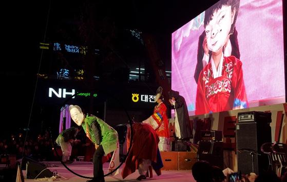 지난해 12월 3일 대전에서 열린 박근혜 퇴진 6차 대전촛불집회에서 마당극패 우금치 단원들이 이장우 국회의원 가면(동그라미)을 쓰고 박근혜 전 대통령을 풍자하는 공연을 하고 있다. [중앙포토]