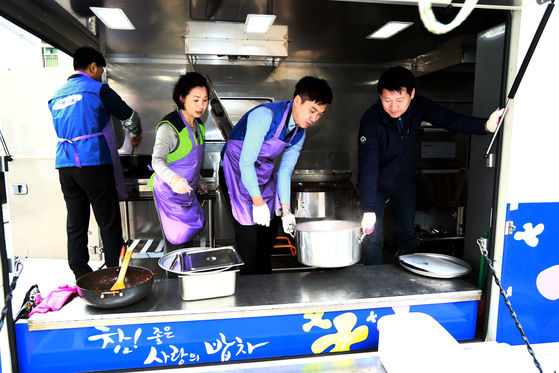 서울 송파구 사랑의 밥차에서 자원봉사자들이 어르신들께 식사를 대접하기 위해 음식을 나르고 있다. [사진 송파구청]