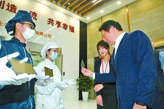 최태원 SK그룹 회장(오른쪽)이 지난해 9월 하이닉스 중국 충칭 공장에서 반도체 제품을 살펴보고 있다. 최 회장은 하이닉스에 강한 애착을 보여왔다.   [사진제공=SK그룹]