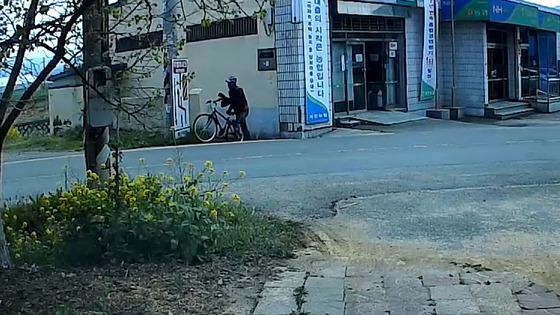 지난 20일 경북 경산시 자인농협 하남지점에서 권총을 들고 들어가 1563만원을 훔친 범인이 자전거를 타고 달아나고 있다. [사진 경산경찰서]