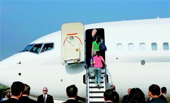 2009년 8월 빌 클린턴 전 미국 대통령은 방북해 북한에 억류된 미국인 기자 로라 링(초록색 상의) 과 유나 리(분홍색 상의)씨에 대한 석방협상을 벌였다. 사진은 석방된 미국인 기자 2명이 평양 순안공항에서 전세기 트랩에 오르는 모습. [ 평양 로이터 뉴시스 ]