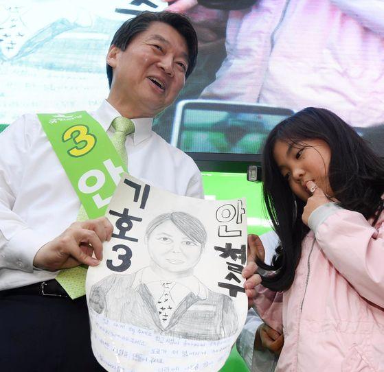 국민의당 안철수 대선후보가 27일 오후 대구 동성로 대구백화점 인근에서 선거유세 중 한 어린이가 그린 포스터를 보며 미소를 짓고 있다. [중앙포토]