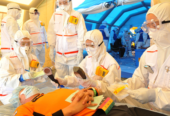 지난해 한국원자력연구원에서 열린 방사능방제합동훈련에서의료진들이방사능에 오염된 소방관을 치료하고 있다. [중앙포토]